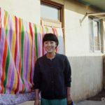 Yo Sun-cha  standing in front of one of the beautiful quilts ubiquitous in Korea.