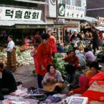 Locals  watch as a gentleman makes his purchase in a busy Chonju marketplace         1/2